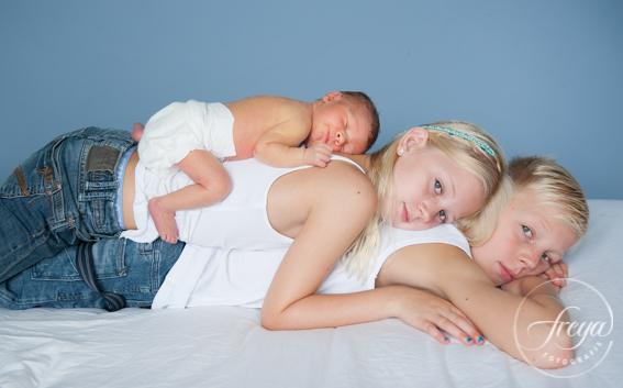 Newborn baby met grote broer en zus op de foto