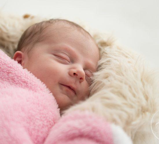 newborn baby met glimlach