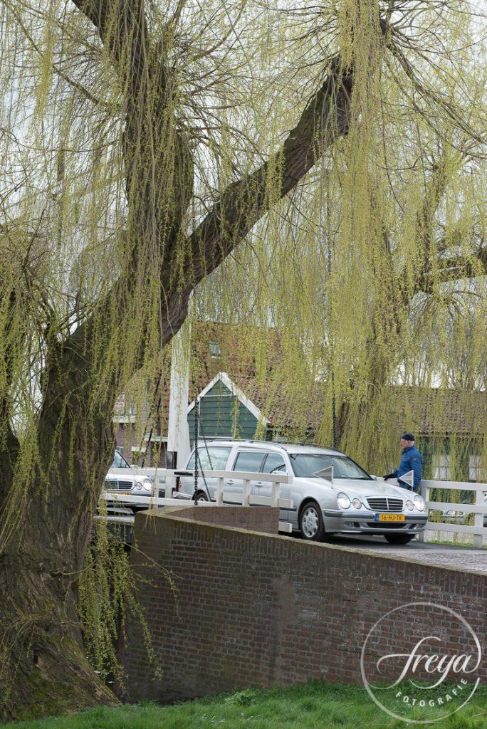Rouwauto rijdt over ophaalbrug in Edam door treurwilgen omgeven