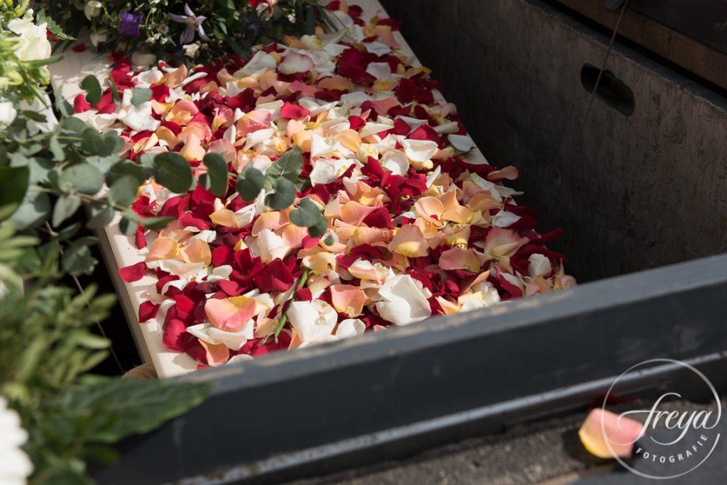 De kist wordt bedekt met bloemblaadjes