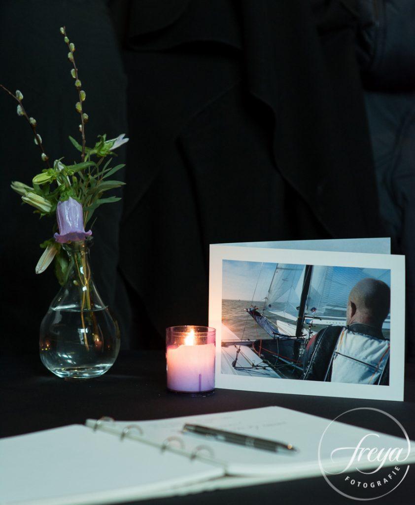 Condoleance register met rouwkaart, kaars en bloemen