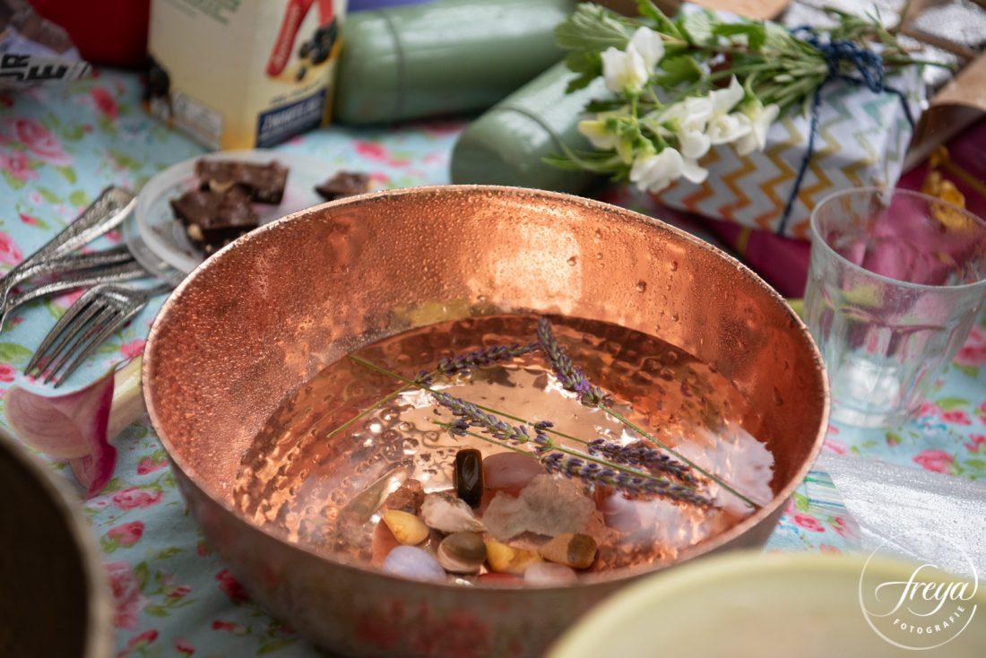 Koperen schaal met water, halfedelstenen en lavendel