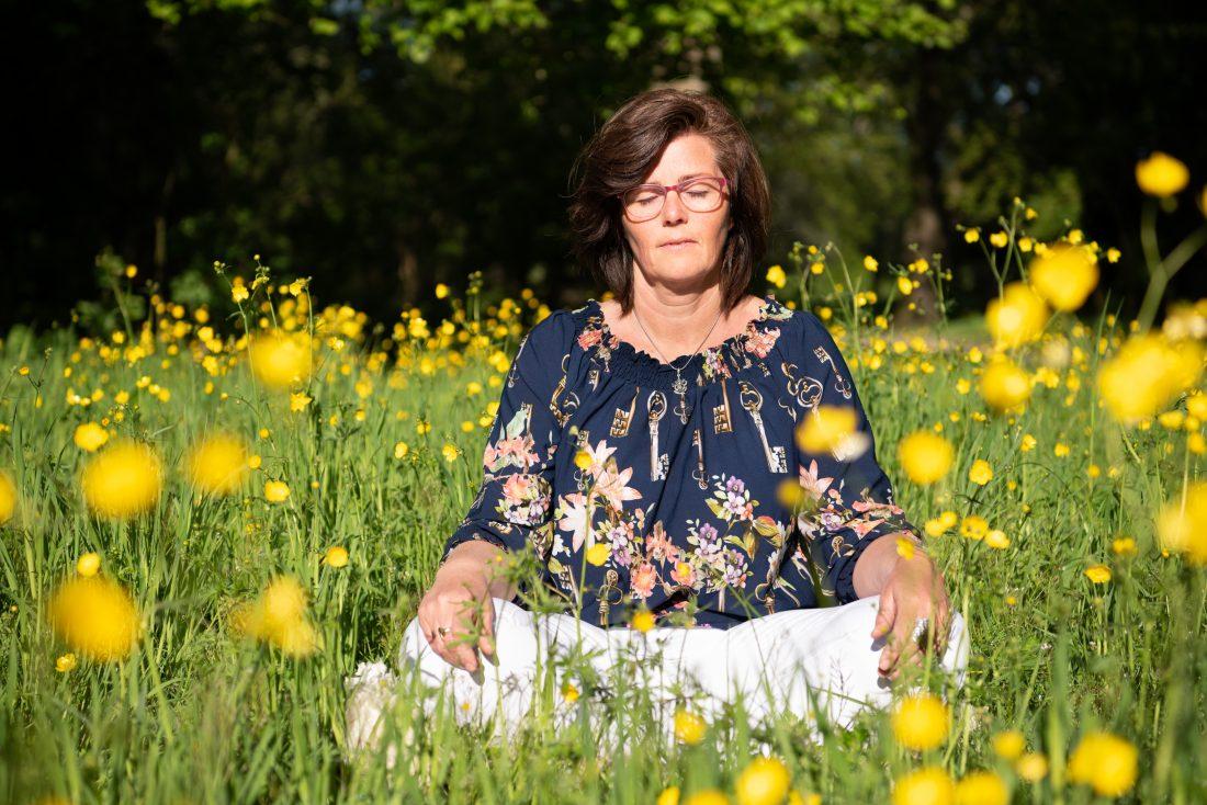 mediterende vrouw tussen boterbloemen