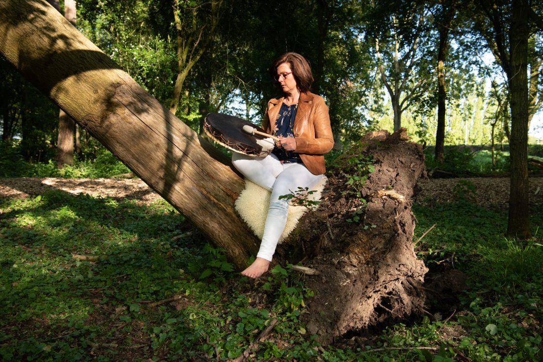Therapeute op ontwortelde boom speelt medicijndrum