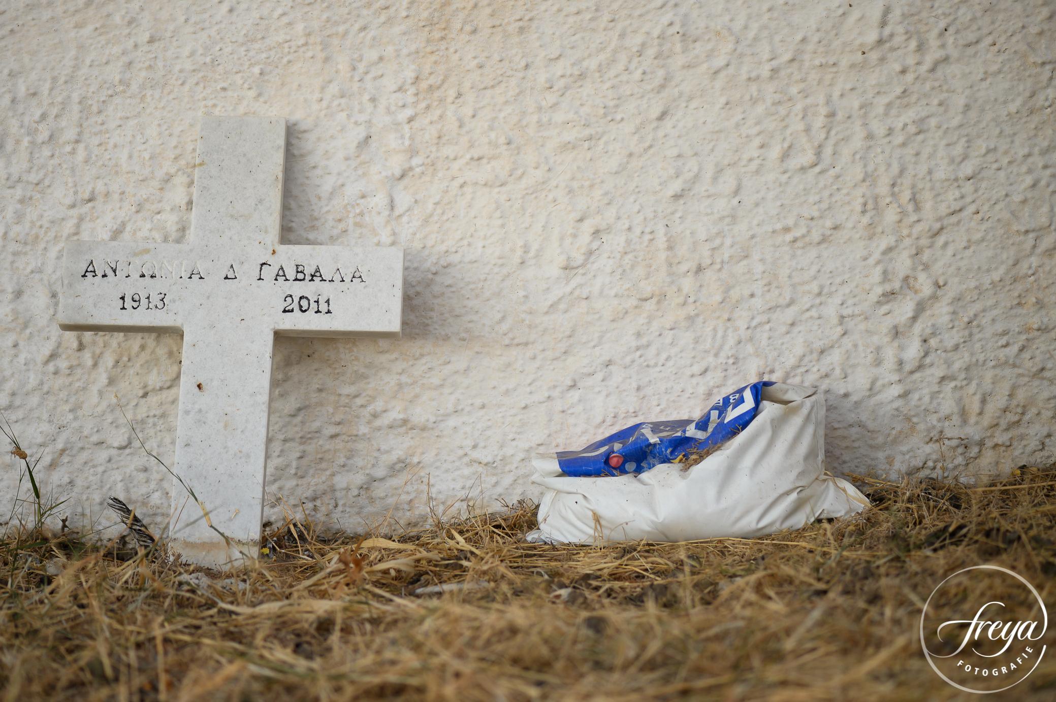 Een kruis van een recent geruimd graf leunt tegen de muur van het kleine kerkhof