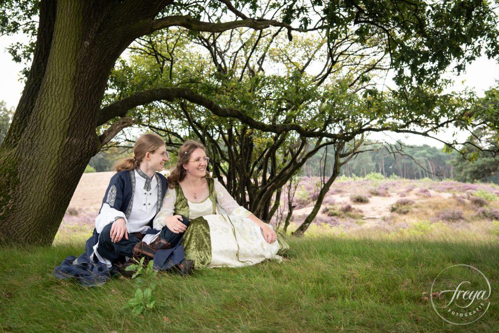 Bruidspaar zit onder boom met heide op achtergrond