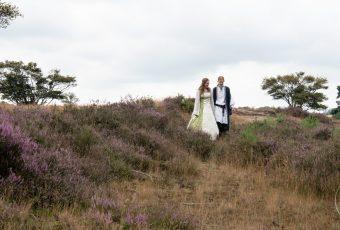 Bruidspaar in keltische kledij loopt hand in hand over de heide