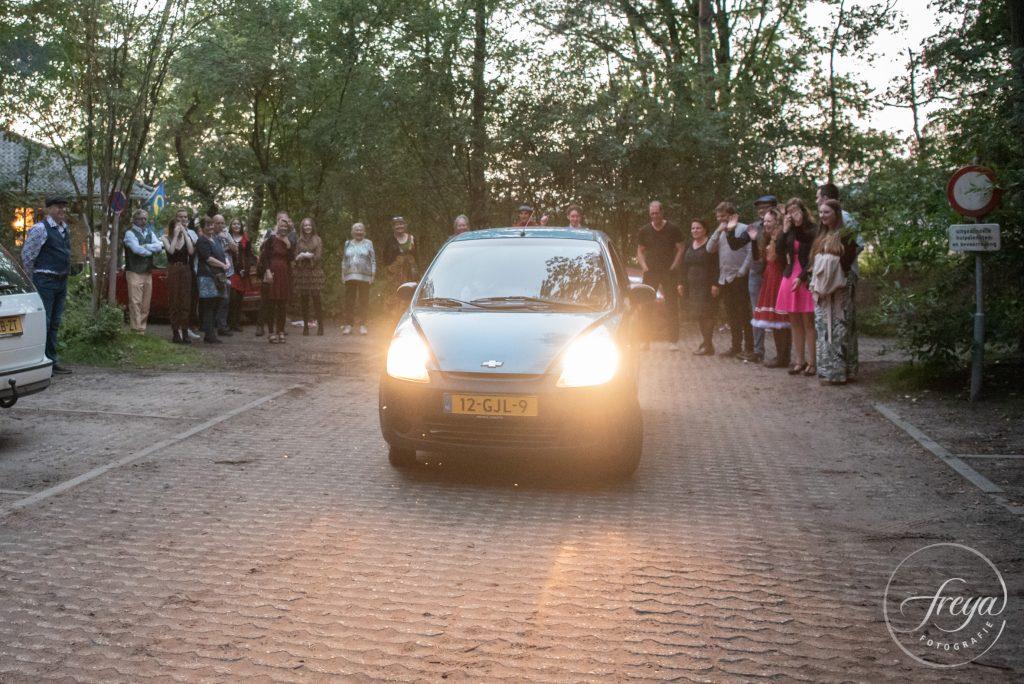 Auto met bruidspaar rijdt weg bij 't Bluk, nagezwaaid door de gasten.