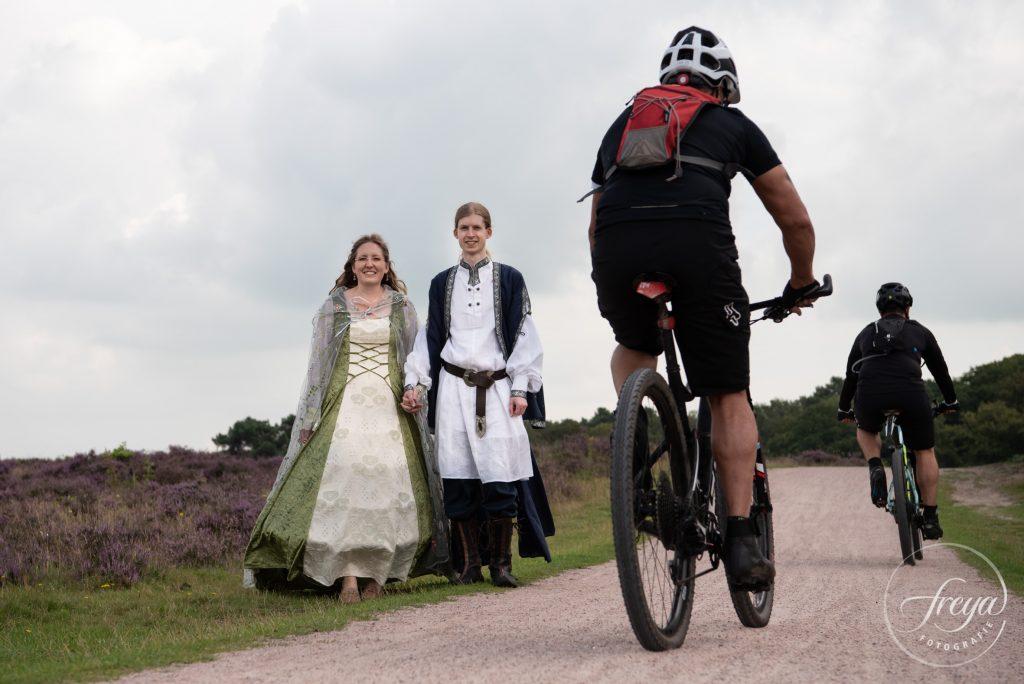 Bruidspaar stapt even opzij op de heide omdat er mountain bikers langs fietsen