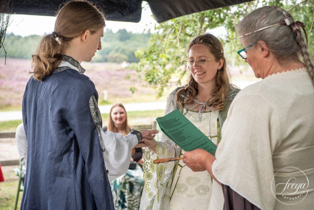 Bruid leest de hand van bruidegom tijdens pagan handvasten