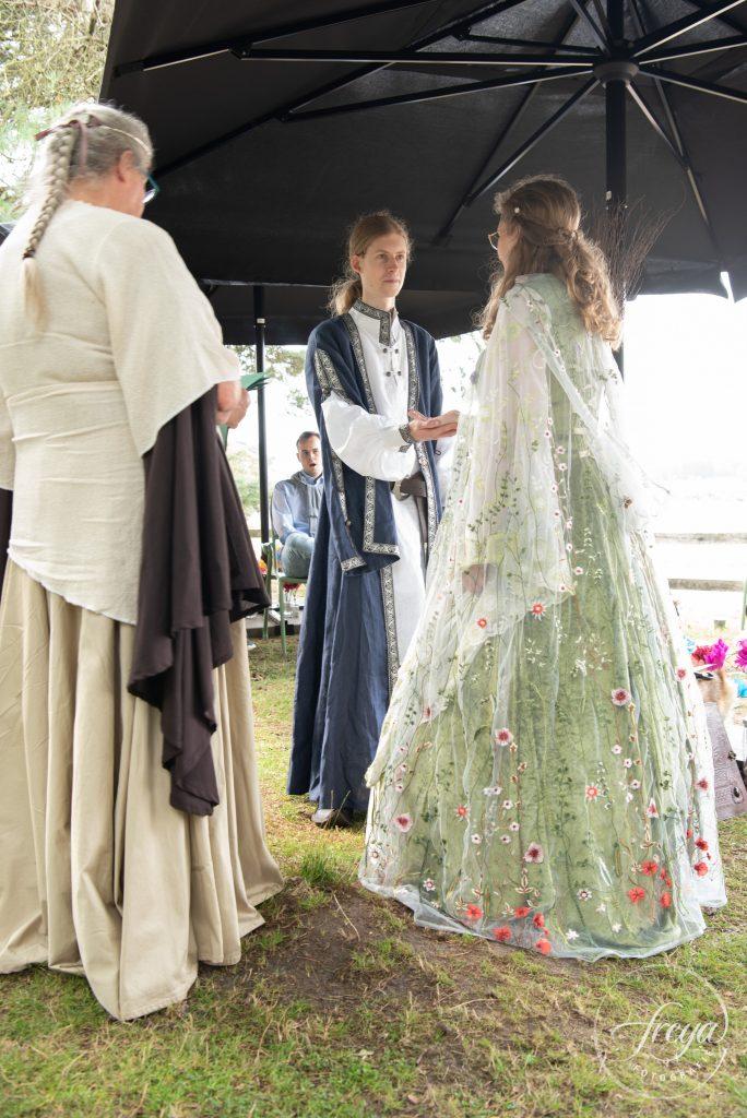 De bruid heeft een prachtige cape met geborduurde bladeren en bloemen aan